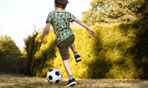 Boy playing football outside