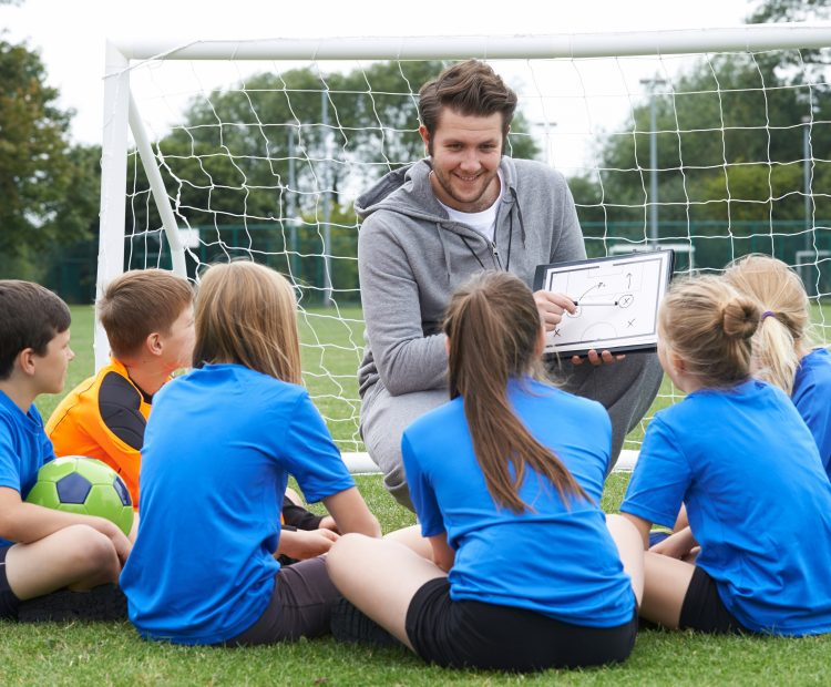 Coach with clipboard in front of goal with kids