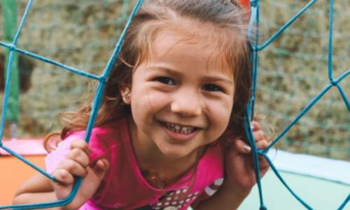 Girl playing on outdoor equipment