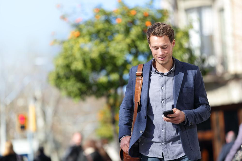 man walking and using phone
