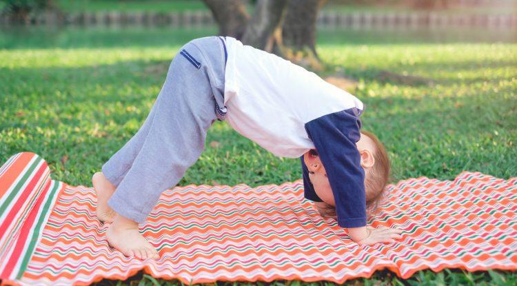 Little boy doing yoga outdoors