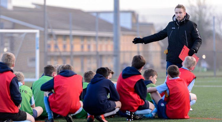 Male football coach with boys