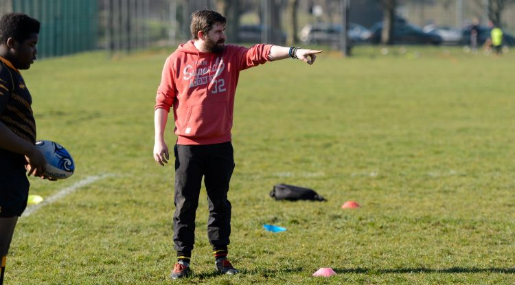 male rugby coach points finger