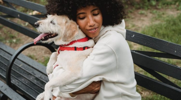 Lady hugging a dog whilst exercising outdoors
