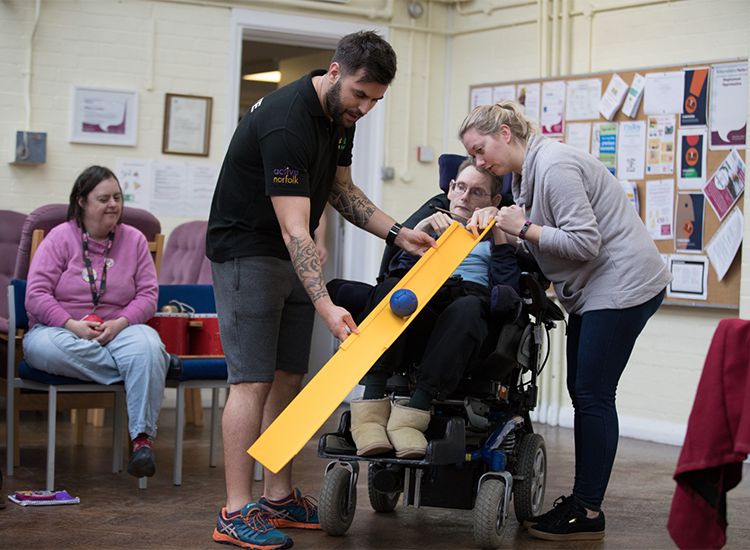 man and centre staff worker hold ramp for disabled man to play bowls
