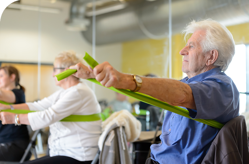 Older man using resistance bands as a group workout