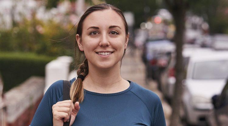 woman with yoga mat walking down city street