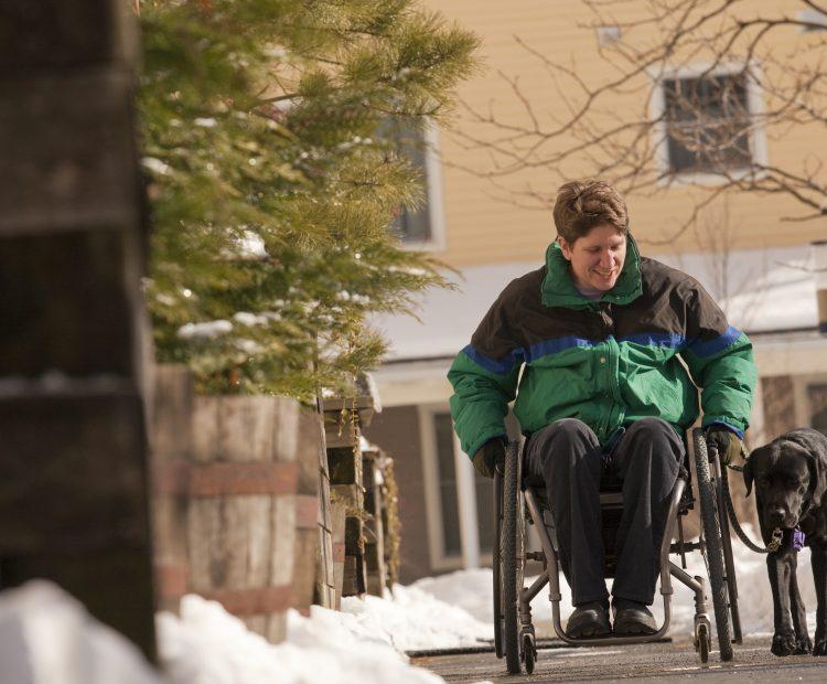 woman in wheelchair walking dog down snowy street