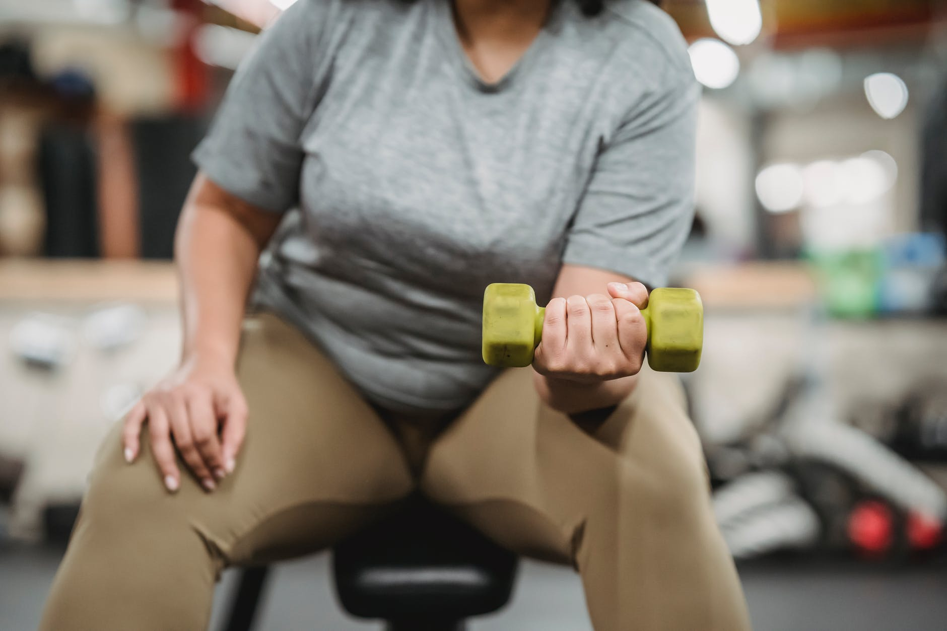 overweight person lifting a handweight for health