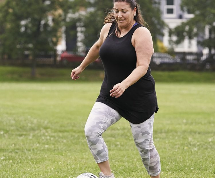 middle aged woman plays football in park