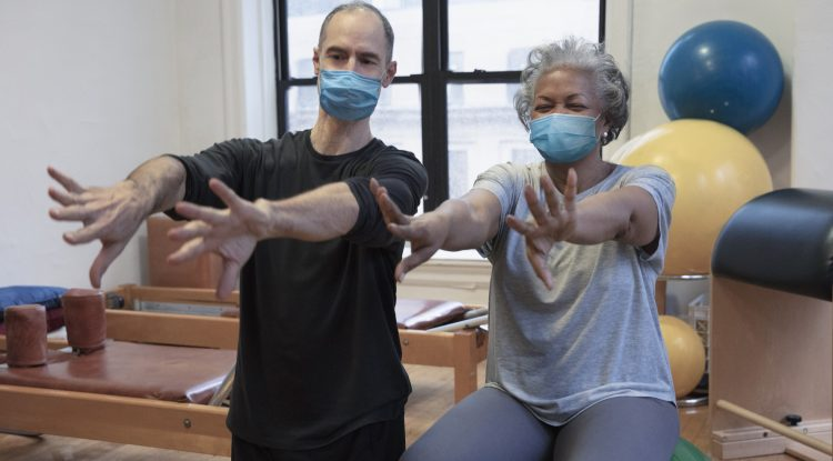 physio and woman exercising with masks