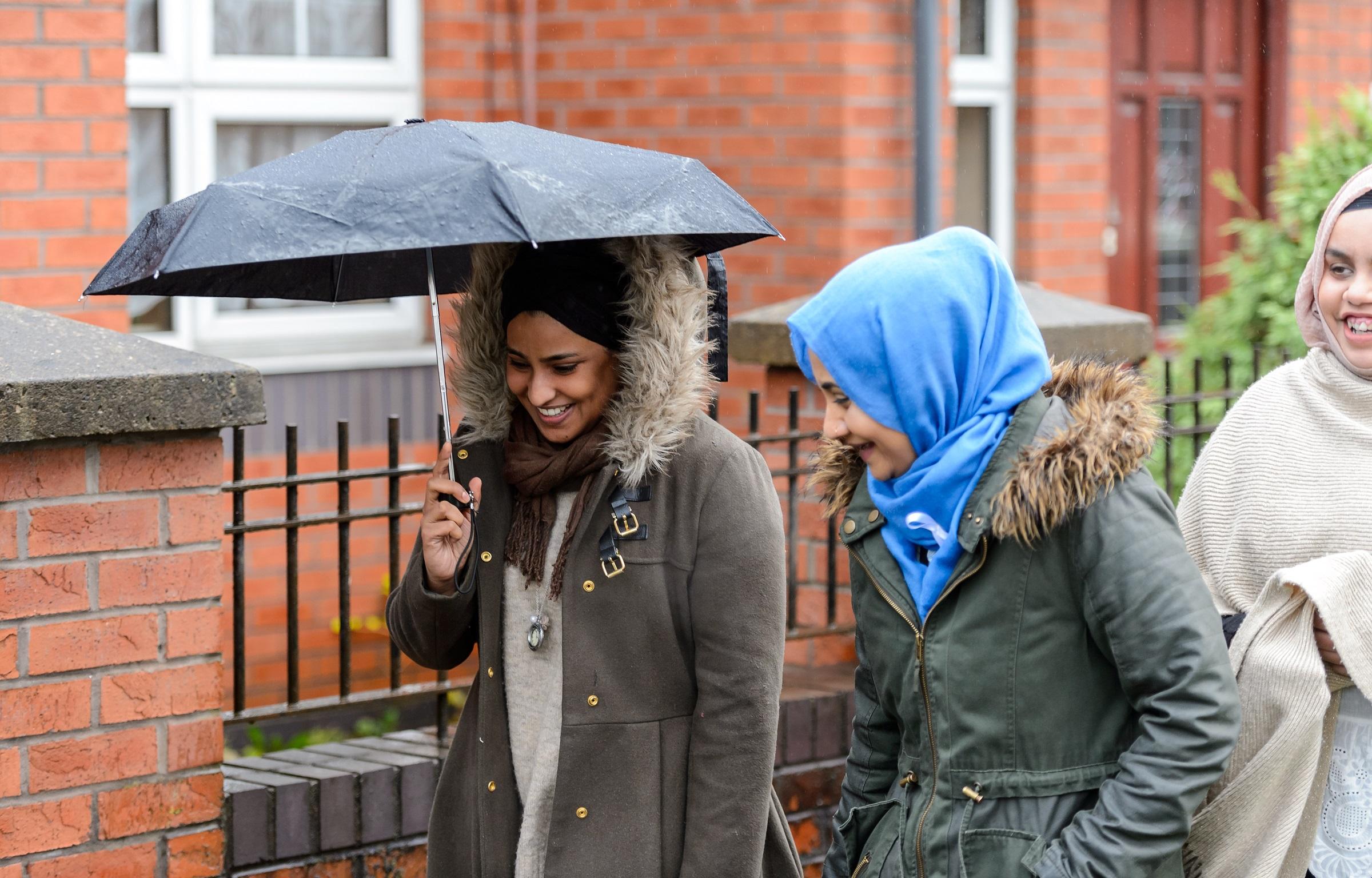 three women walking down street with umbrella