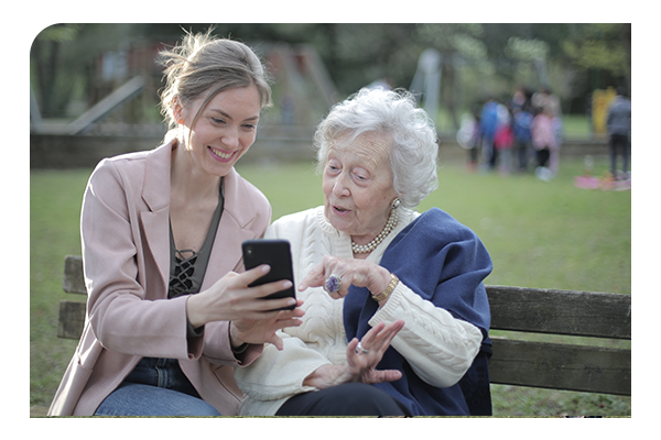 woman sharing phone with older woman