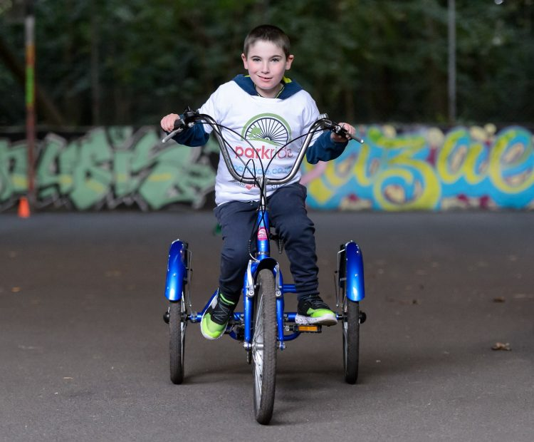 young boy on adapted bicycle