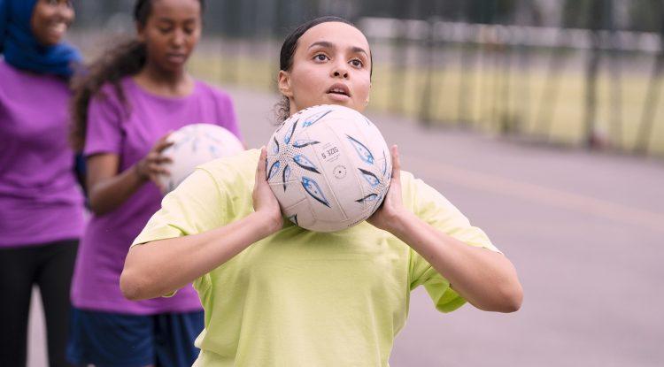 young girl playing netball