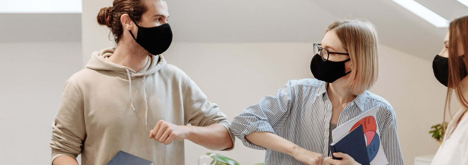 Two employees bumping elbows in the workplace