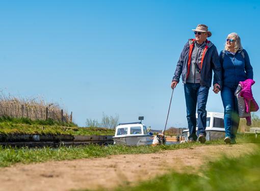Older couple walking along Norfolk broad