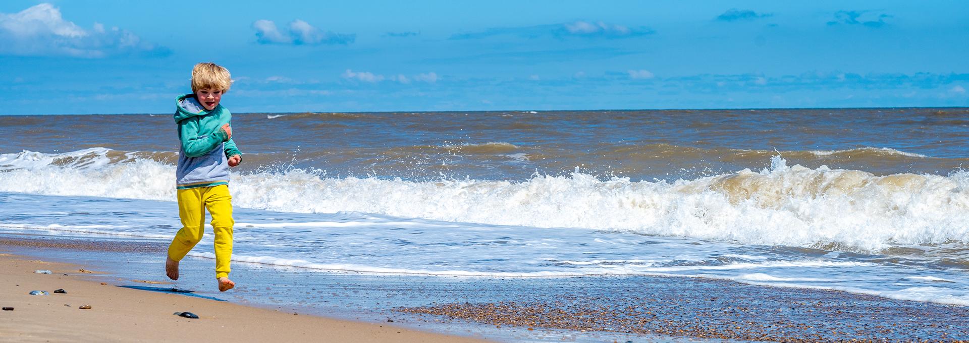 Boy running along a Norfolk beach