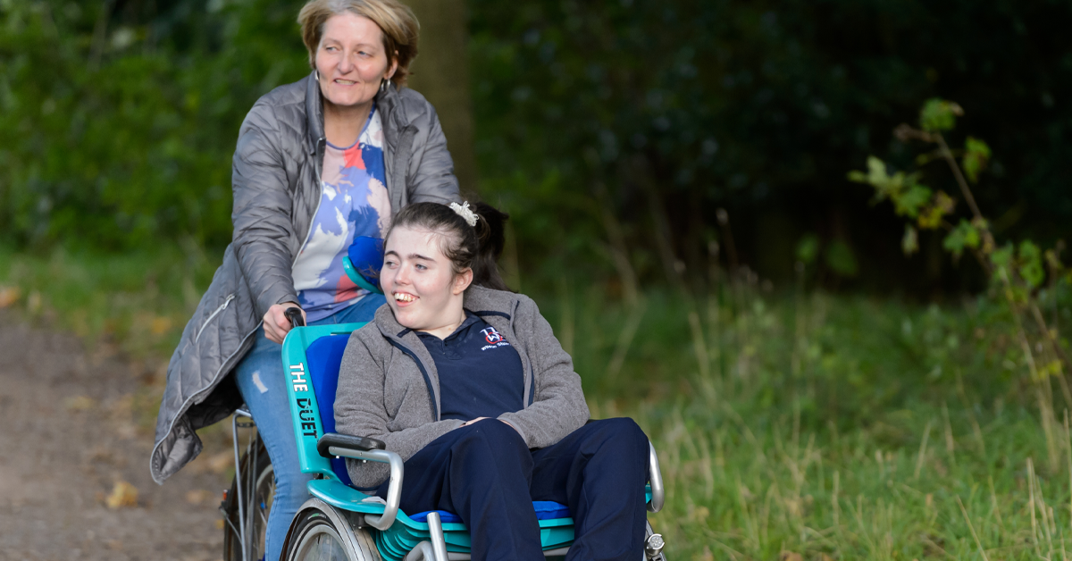 Lady pushing girl in a wheelchair