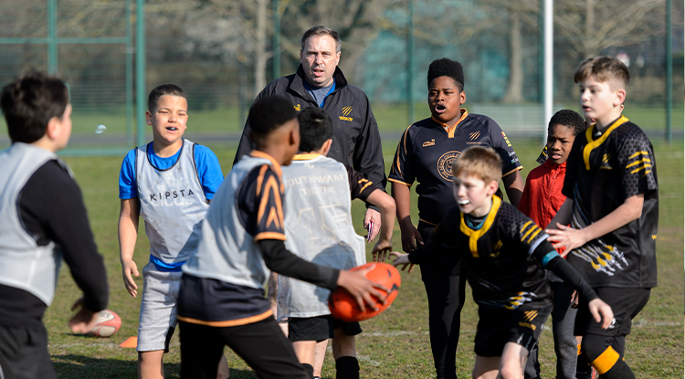 male coach with rugby boys