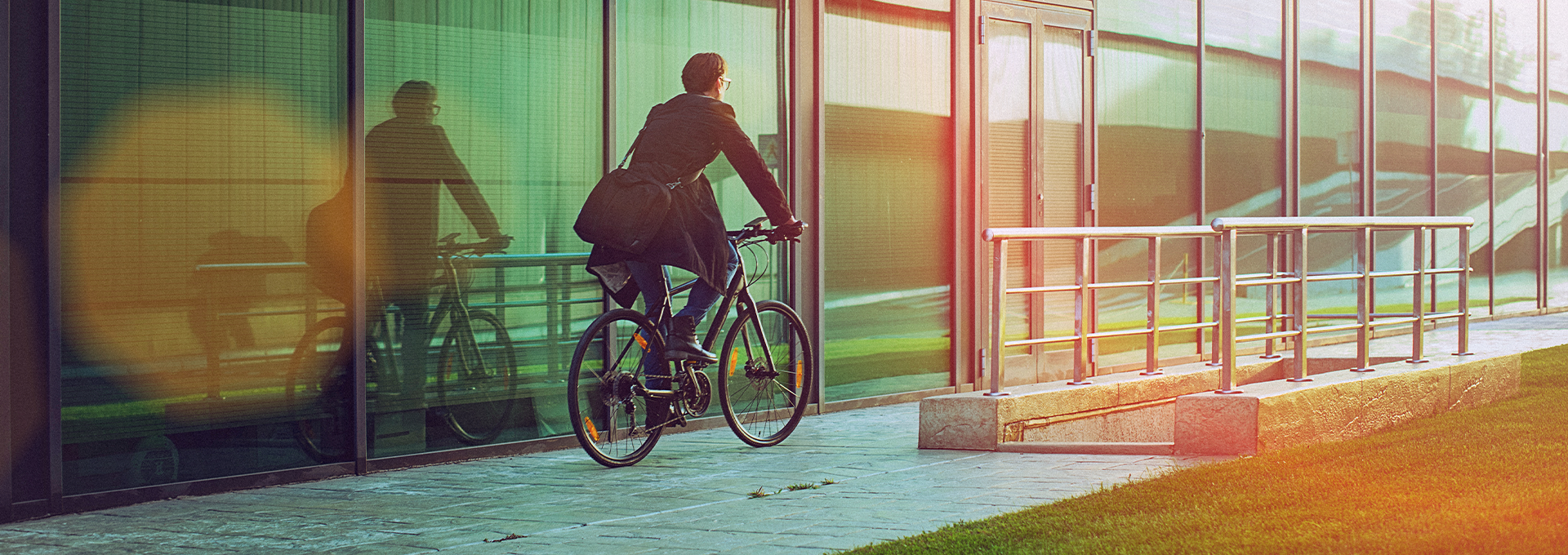 man cycling in front of office building