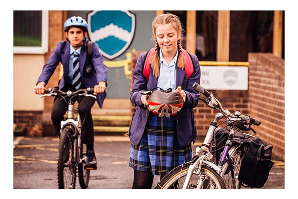 secondary student putting on bike helmet