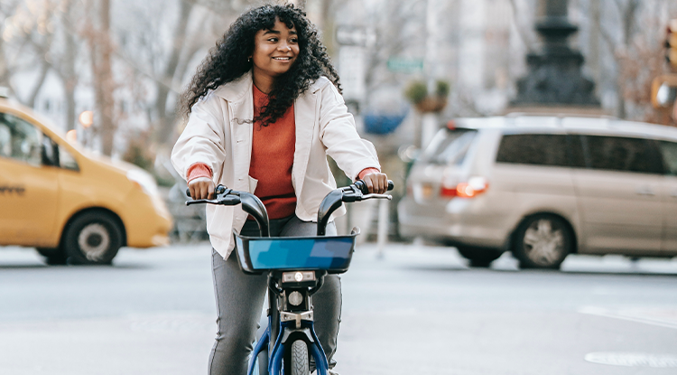 smiling young woman on bike in city