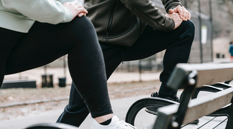 two people stretching legs on a park bench