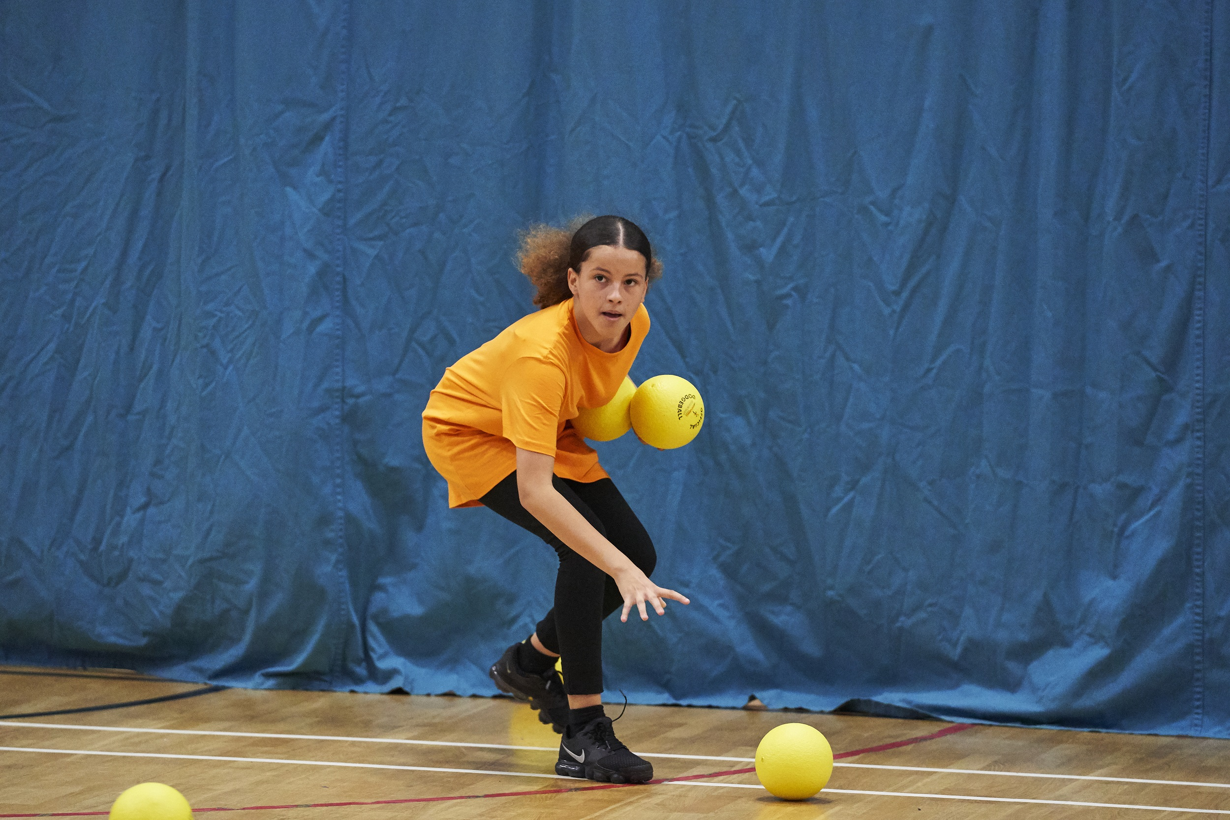 young girl plays dodgeball