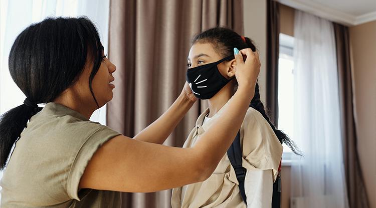 Mum putting mask on girl