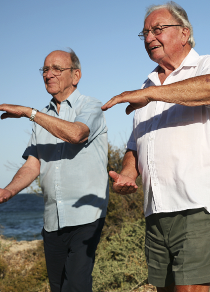 Seniors doing tai chi on the beach